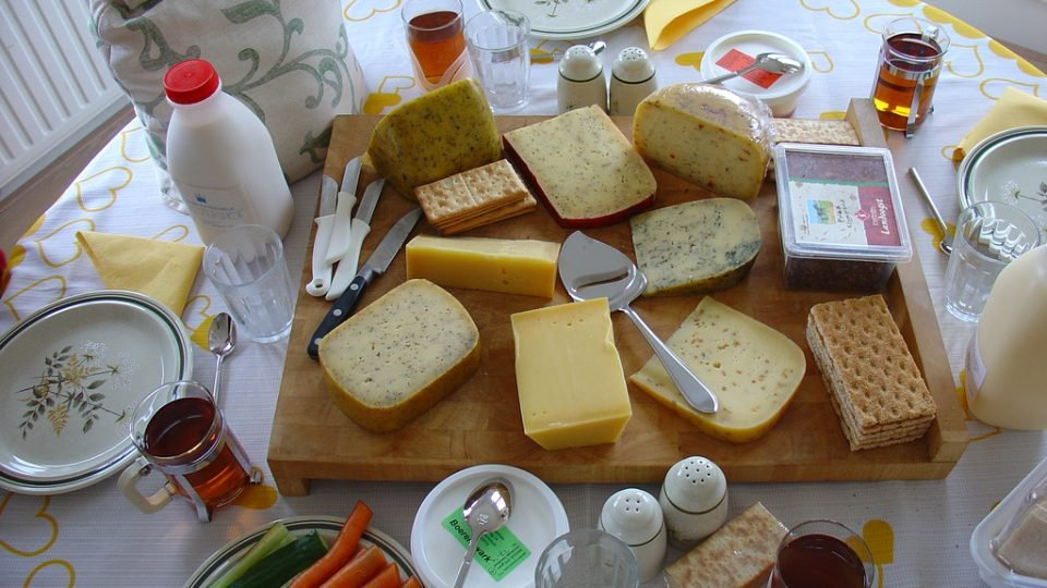 A Table Of Assorted Cheeses And Cheese Implements.