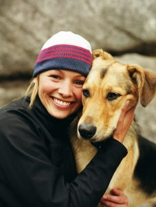 Woman wearing knit cap, hugging dog, portrait