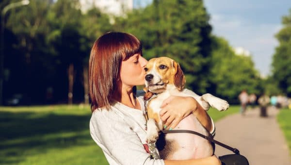 A woman kissing a beagle