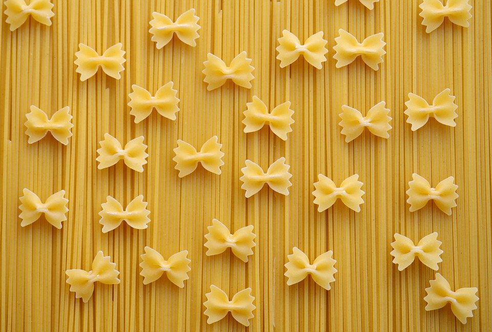 Bowtie pasta on a background of spaghetti.