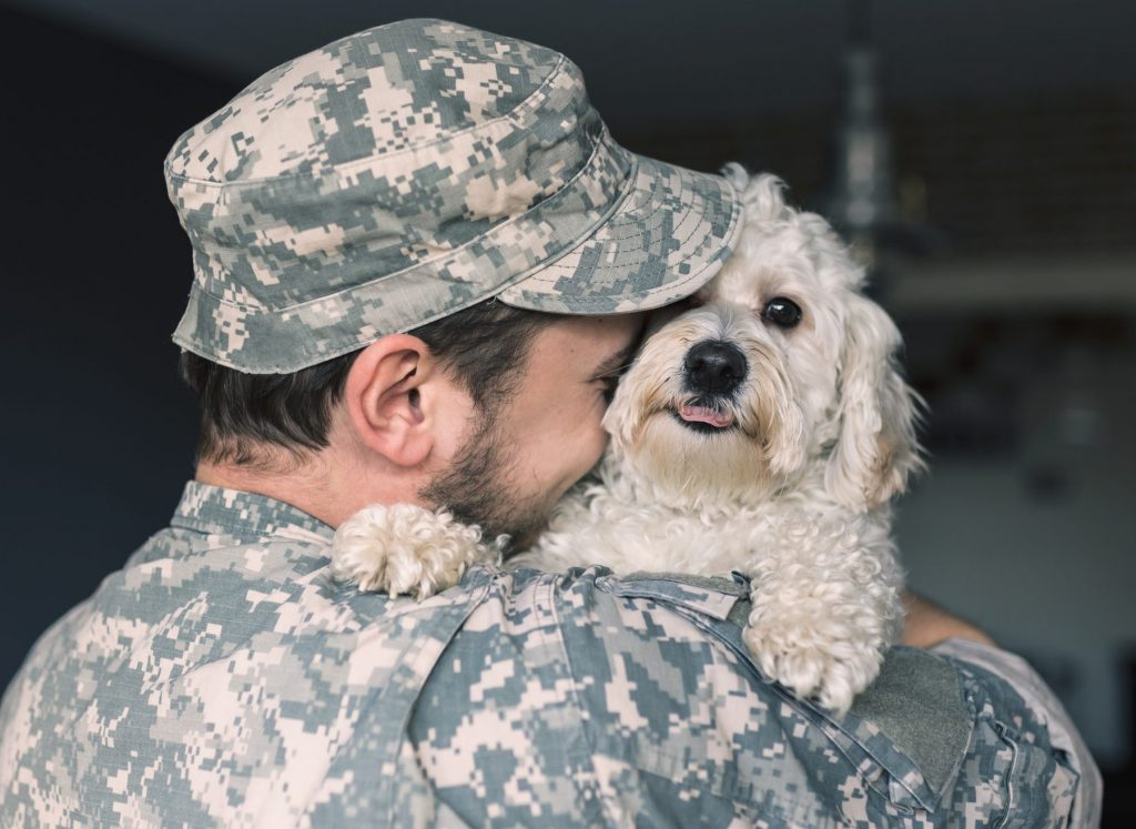 A soldier hugs his service dog.