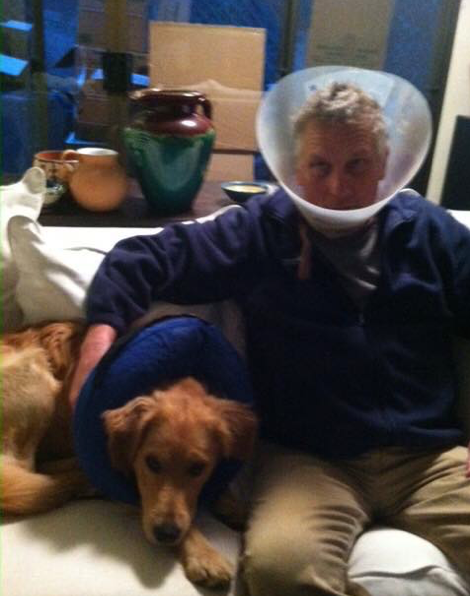 Maxx the dog sits with his human dad, both wearing cones.