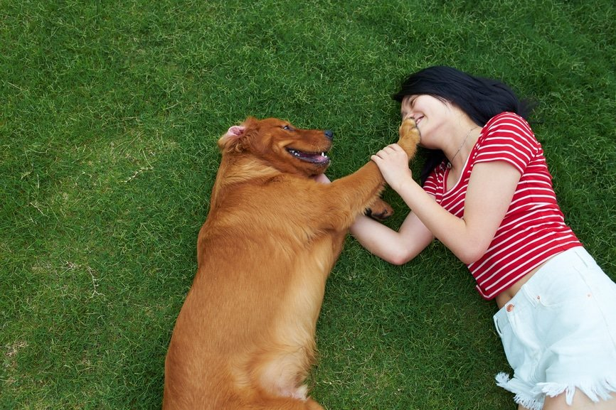 golden retriever names for a smiling golden retriever with woman on grass