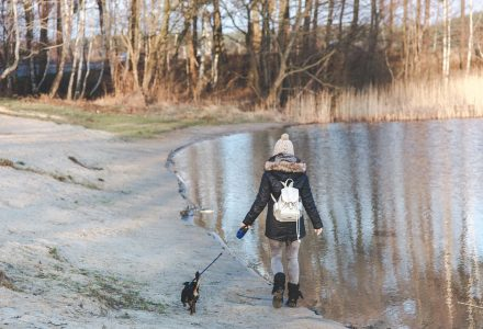 A woman in winter clothing walks a dog outdoors