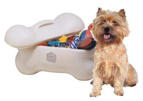 dog sitting next to plastic bone-shaped dog toy storage bin full of toys