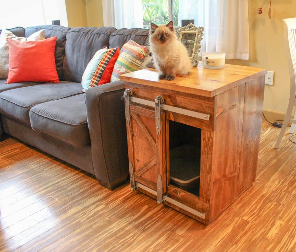 cat sitting on top of rustic cat litter box cabinet with barn door opening