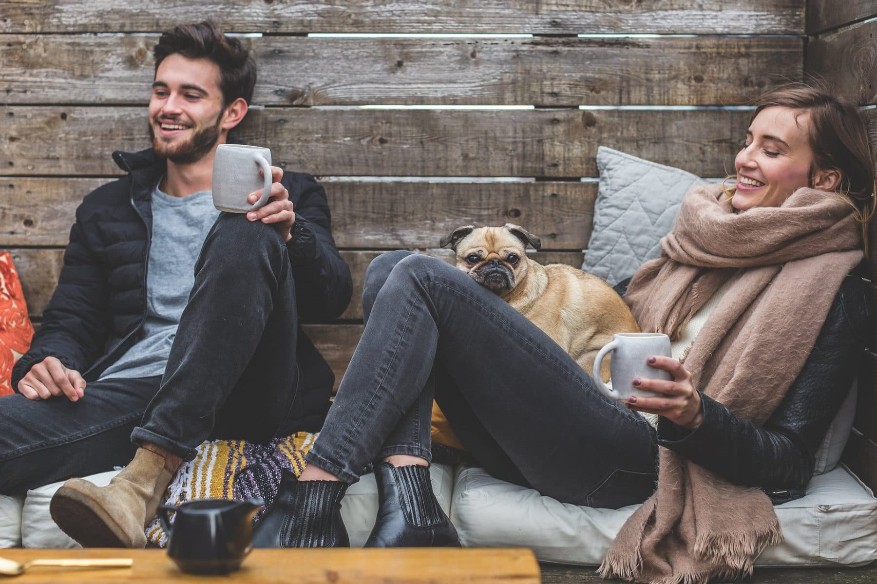 A man and woman enjoying coffee outdoors. A Pug sits on the woman's lap.