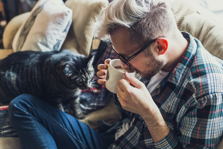 A man drinks coffee with his cozy cat