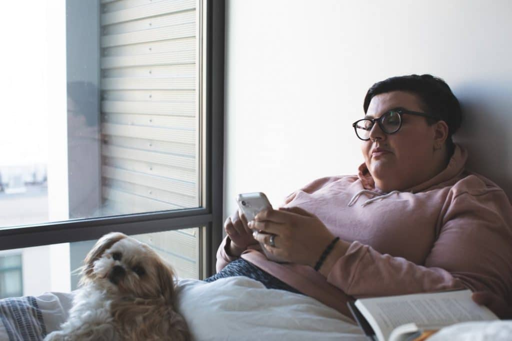 A woman looks at her phone in bed with her cozy dog