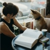 Woman sitting with dog reading in cafe