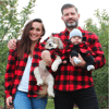 A family and dog wearing matching sweaters