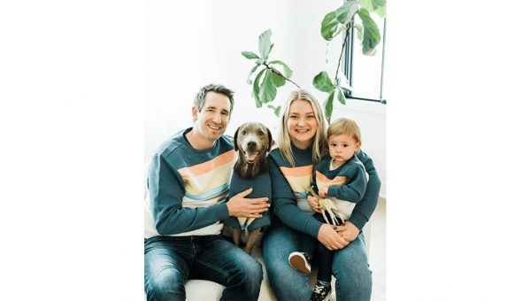 family wearing matching sweaters with their dog
