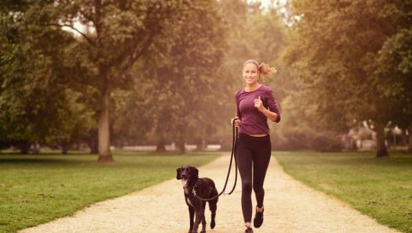 Woman Running with Dog - 123RF