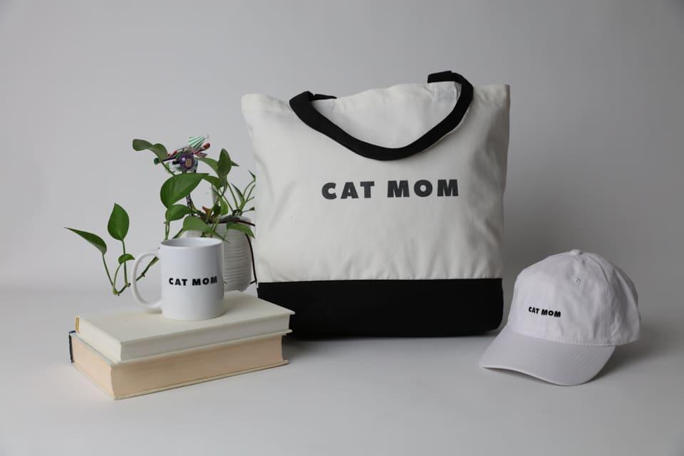 """A mug, tote and baseball cap, all reading, """"Cat Mom"""""""