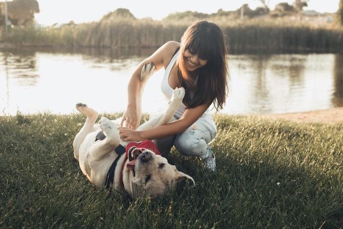 jeune femme qui joue avec son chien au parc