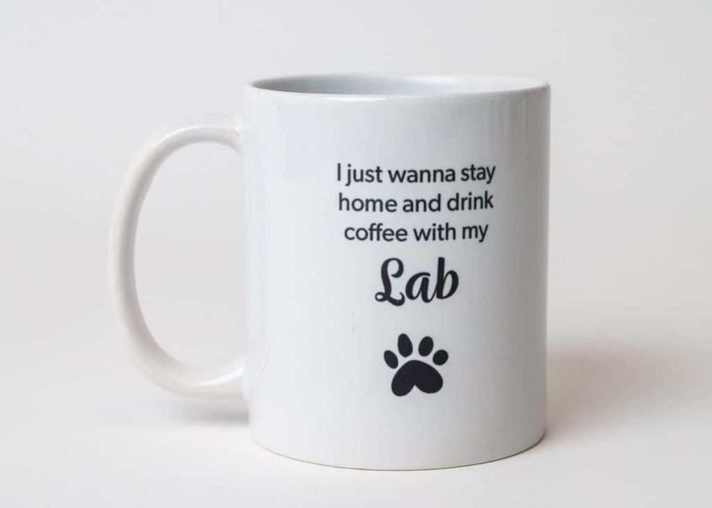 """A mug reading, """"I just wanna stay home and drink coffee with my Lab"""" with a paw print"""