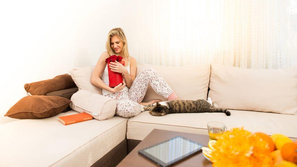 woman on couch with gift and cat lounging