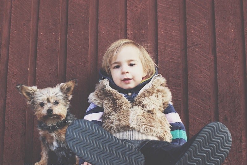 A child and a small dog sitting against a wooden wall.