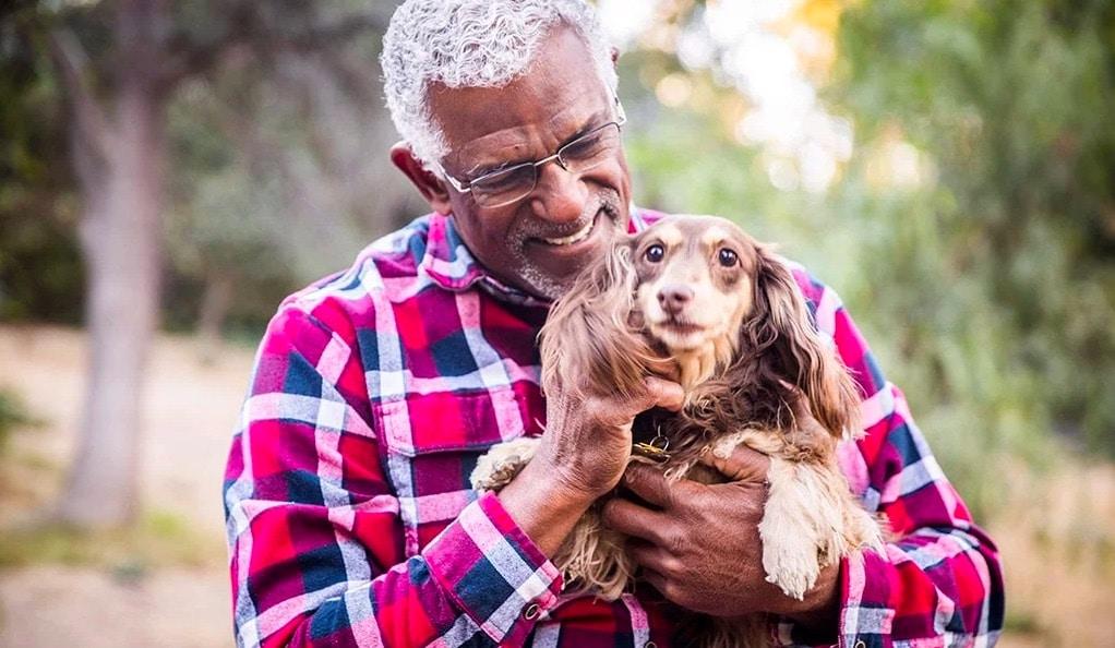 Homme qui porte un chien dans ses bras