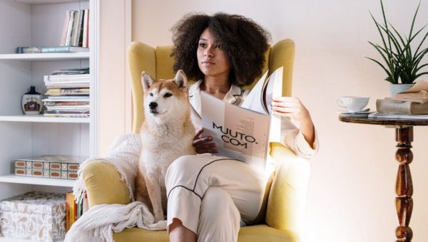 woman sitting in chair in PJs with dog