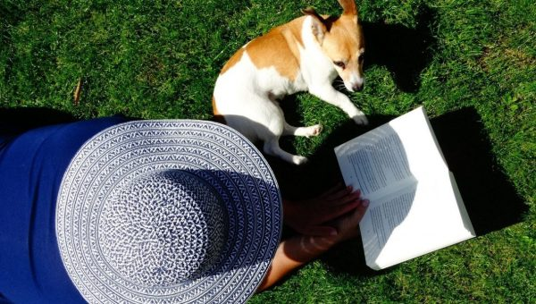 person wearing straw hat and reading with dog