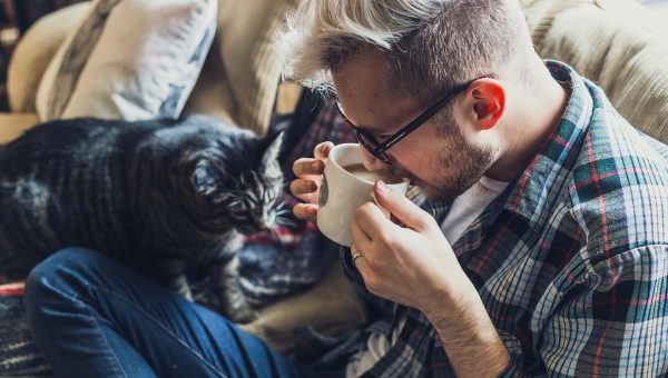 man drinking coffee with cat