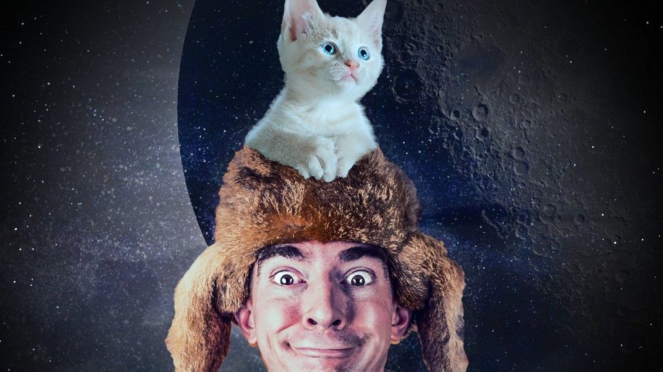 guy wearing fur cap and cat on top of hat