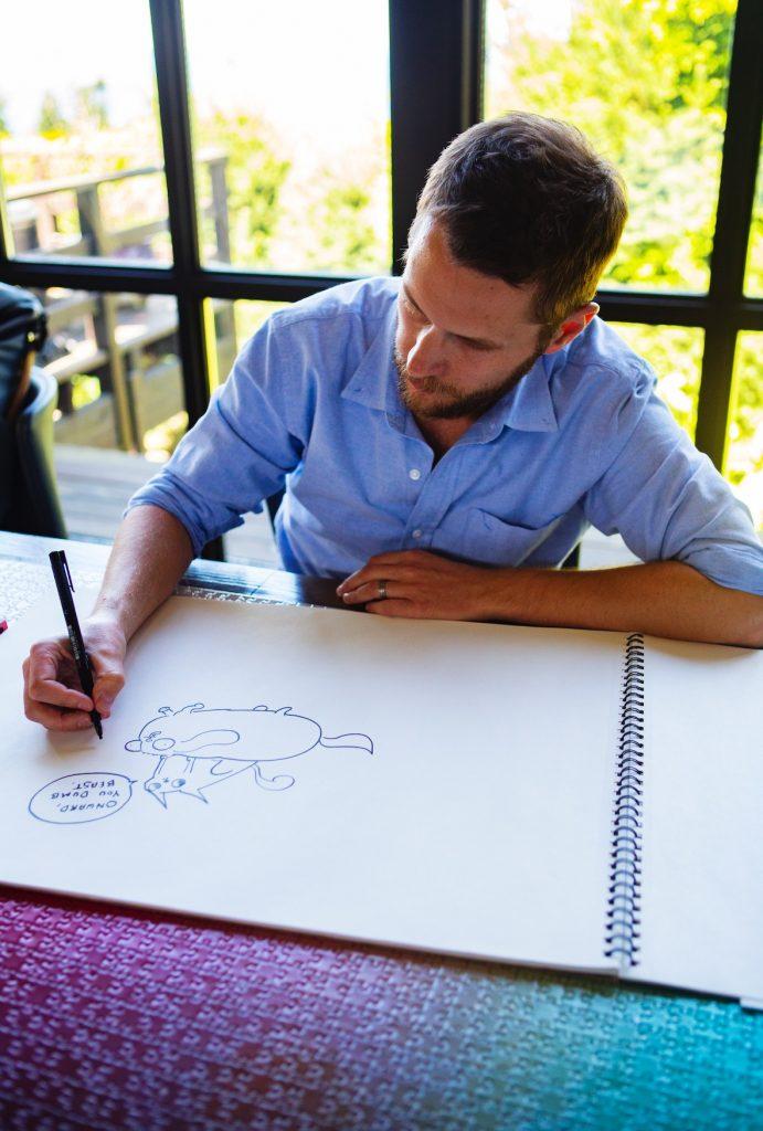 Matthew Inman drawing a cat riding a dog