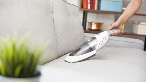 person using handheld vacuum on a couch